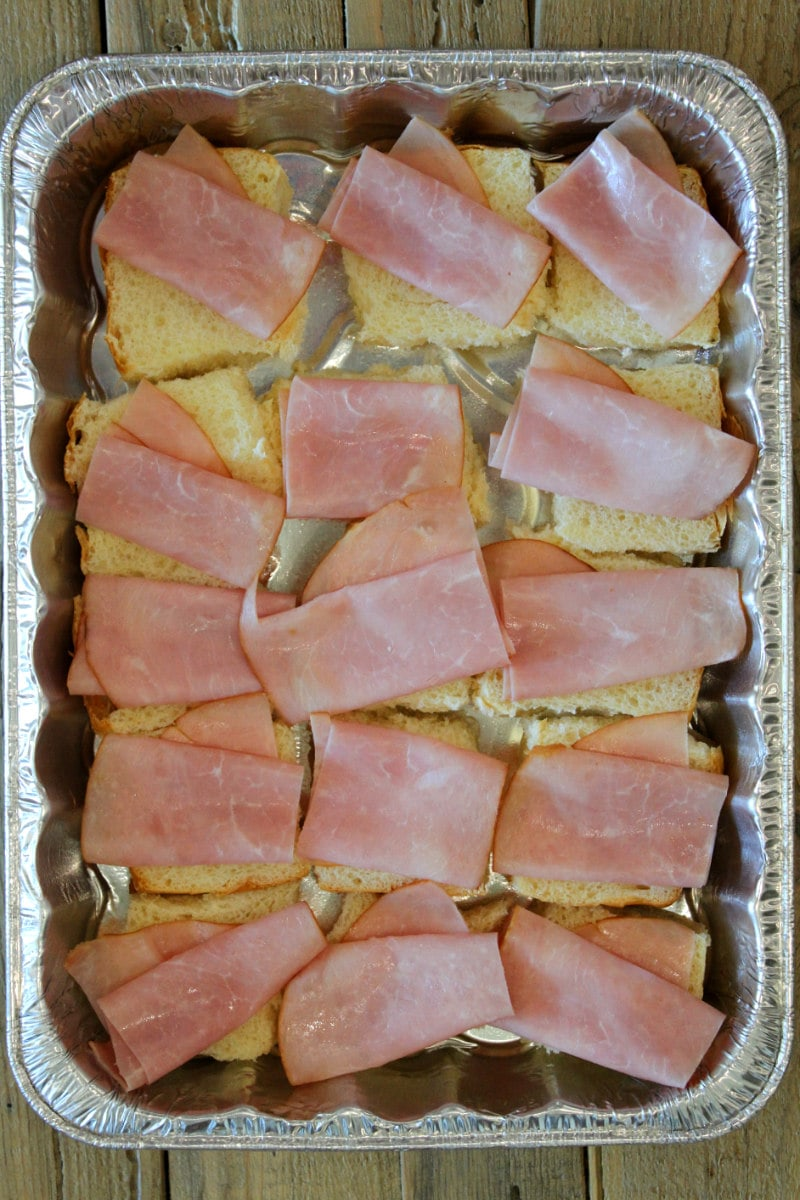 overhead shot of pan of cuban sliders showing process of placing ham on top of buns