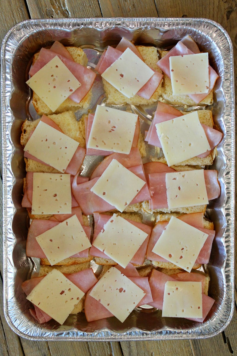 overhead shot of process of making pan of cuban sliders with layers of ham and cheese