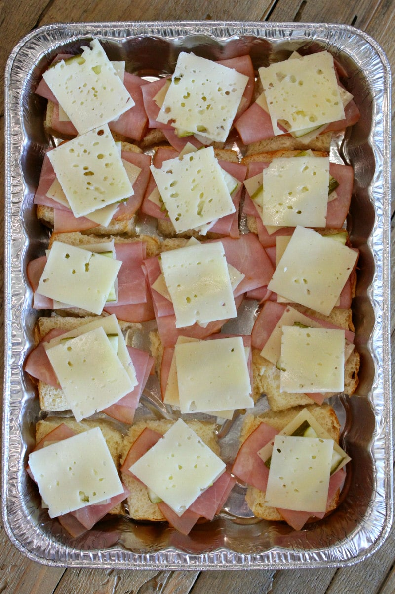 overhead shot of the process of making a pan of cuban sliders with layers of ham and cheese