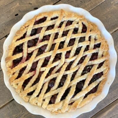 overhead shot of cherry amaretto pie with lattice pie crust on a wooden board