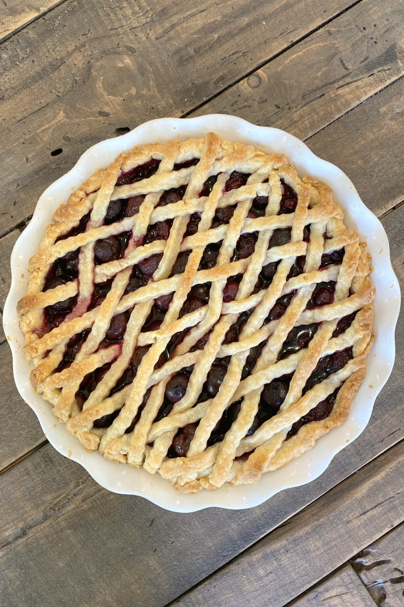 overhead shot of cherry amaretto pie with lattice pie crust on top on a wooden board