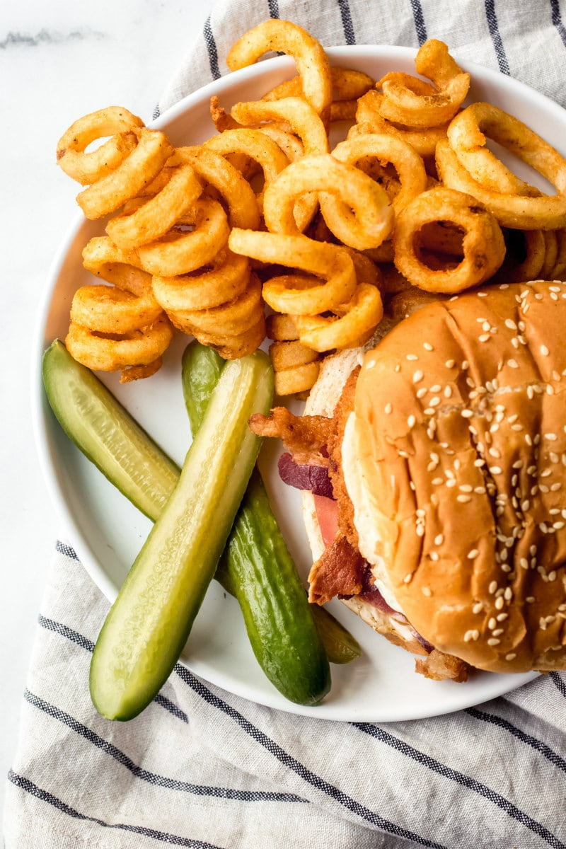 overhead shot of pickles served with curly fries and a burger served on a white plate