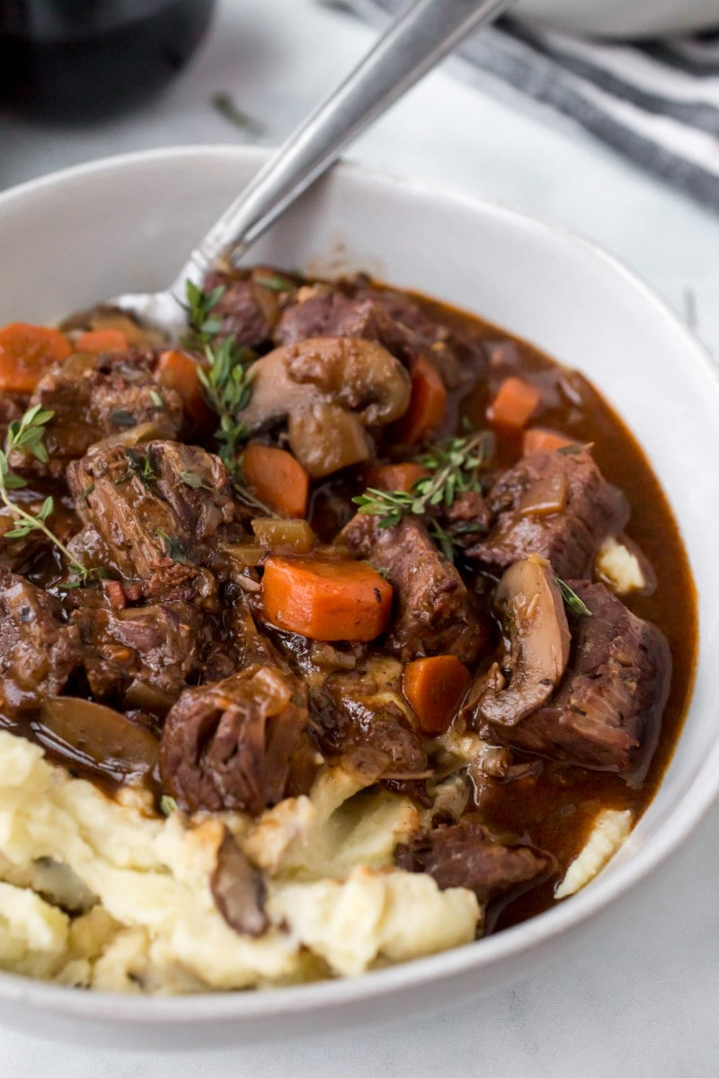 serving of beef bourguignon with potato in a white bowl
