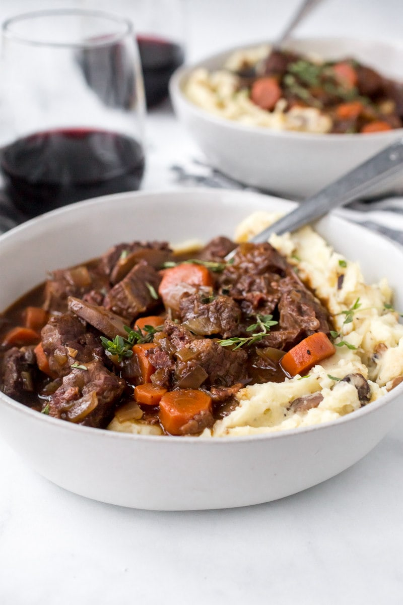 serving of beef bourguignon with mashed potato in a white bowl