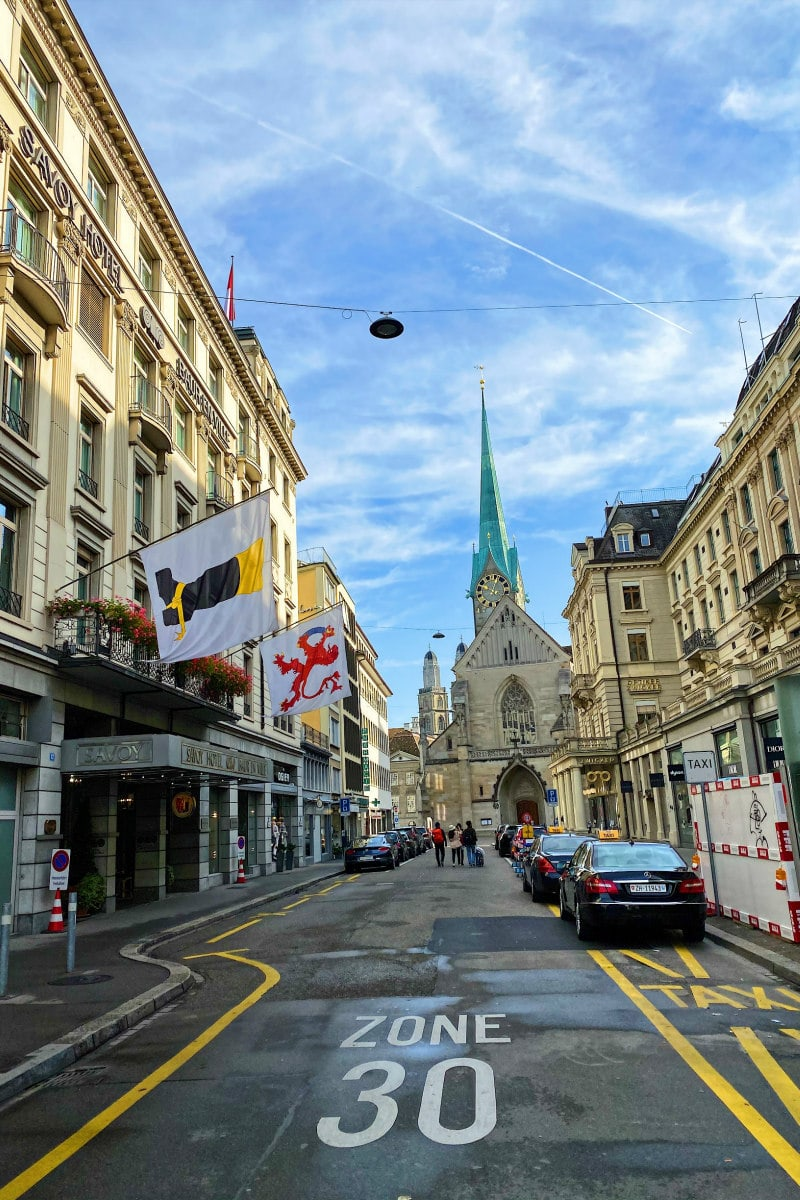 streets of Zurich, Switzerland: city street with cars parked on side and hotel with flags displayed. Church spier in background.