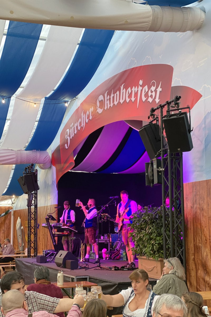 Oktoberfest in Zurich, Switzerland- musicians on stage and people toasting with beer