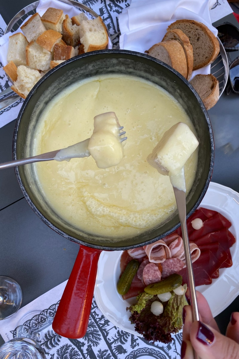 Eating chunks of bread dipped in a pot of cheese fondue