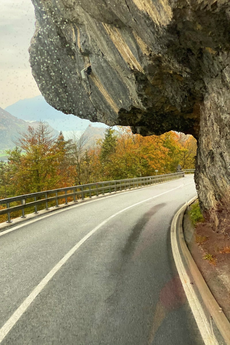 View of the highway to the Swiss Alps with large rock formation hanging over the road