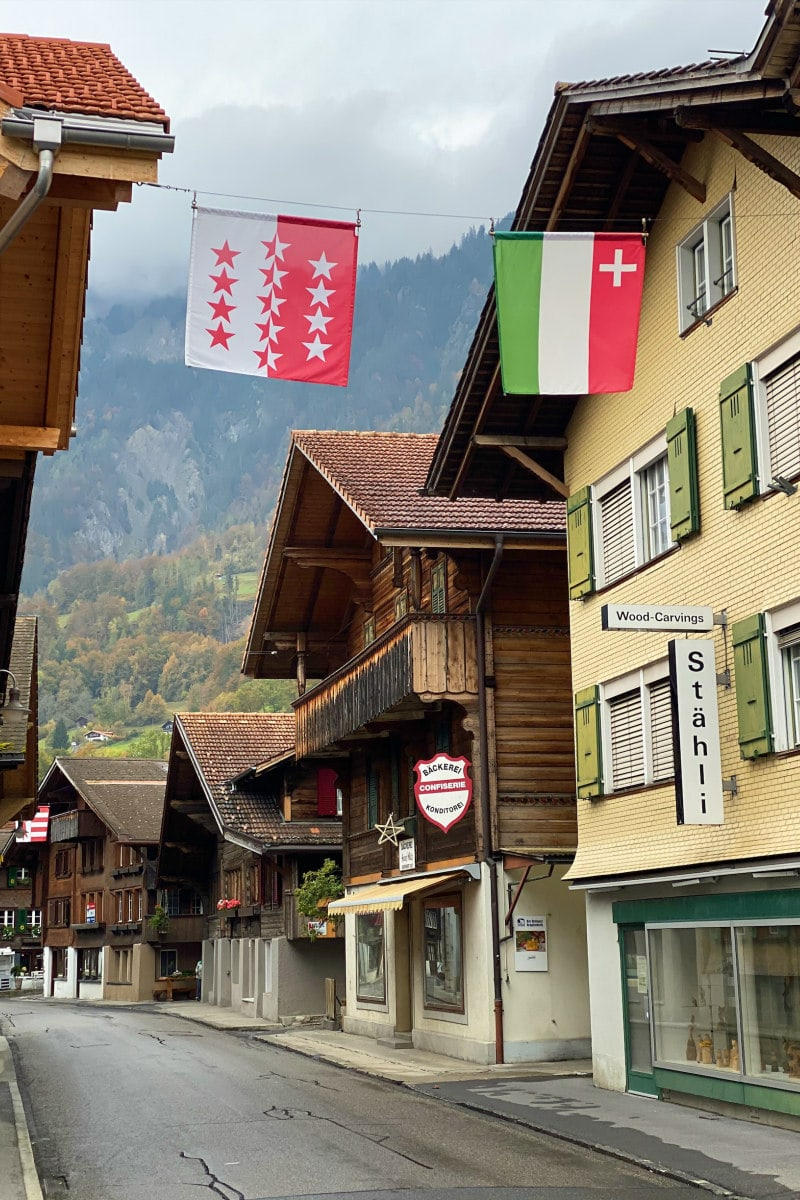 Looking down the main street of the Village of Brienz, Switzerland. Storefronts and flags hanging