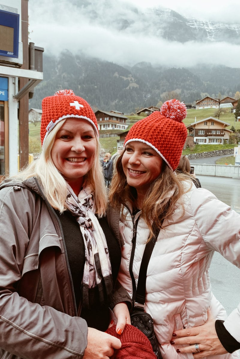 Two girls with red ski hats posing for a photo Below the Swiss Alps