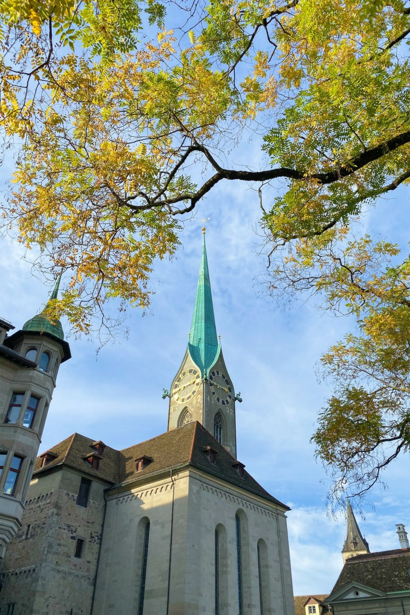 Looking up at a church spier in Zurich through the trees