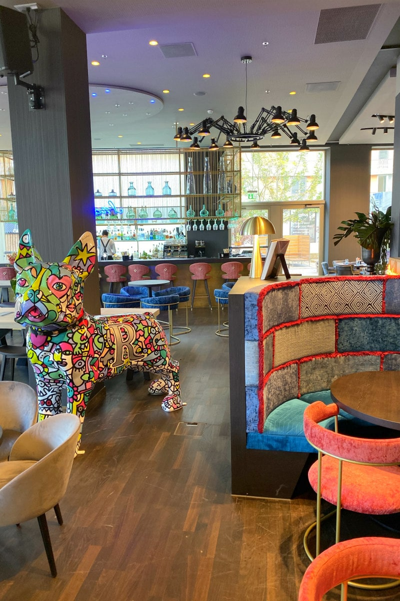lobby of the Renaissance Zurich Tower Hotel with colorful art dog piece and lobby bar and tables
