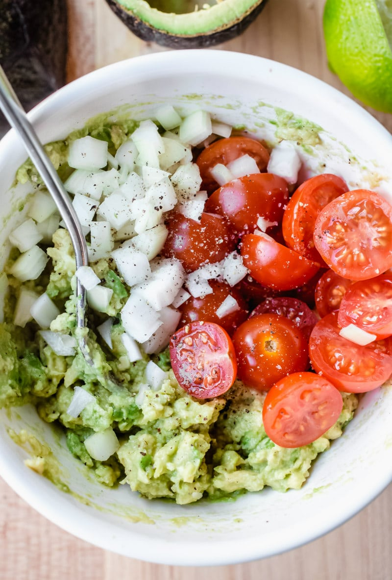 making filling for stuffed avocados (onion, avocado, tomato in a white bowl)