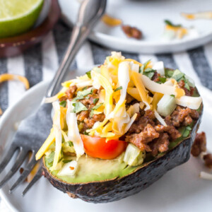 half an avocado stuffed with taco filling. On a white plate with a fork.