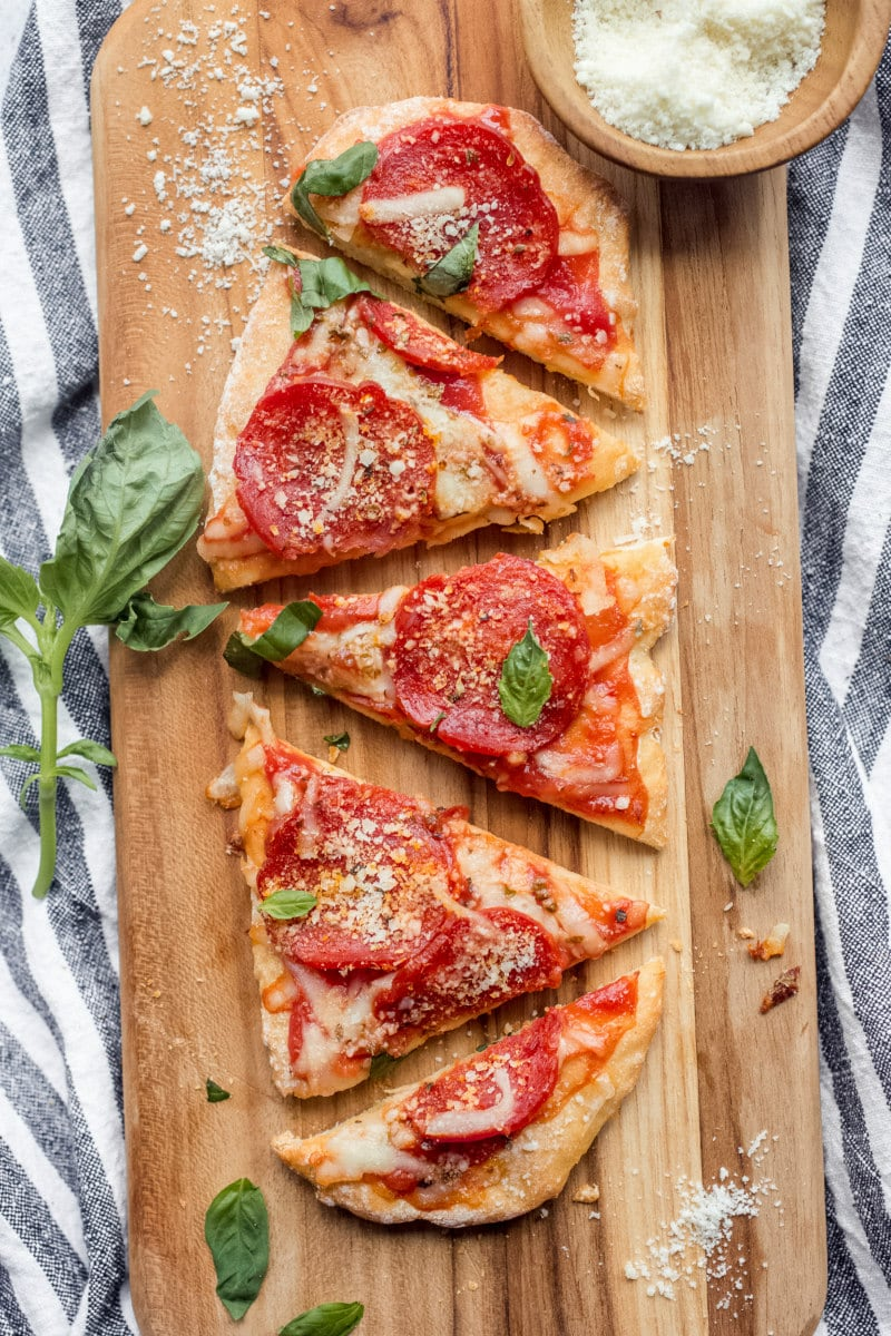 Sliced Weight Watchers 2 Ingredient Pizza with pepperoni on a cutting board set on a white and gray striped napkin