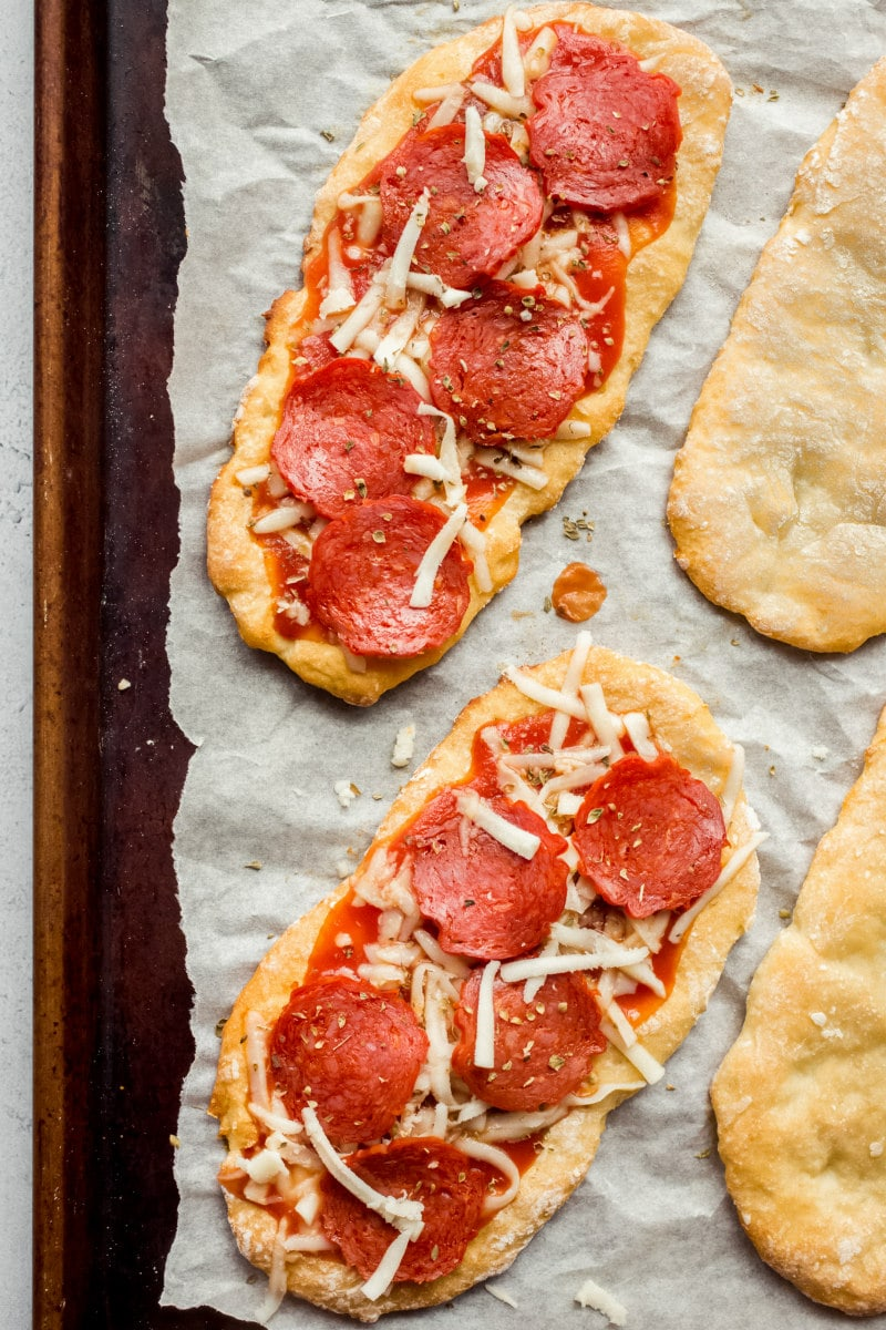 making Weight Watchers Pepperoni Pizzas on a baking sheet ready for the oven