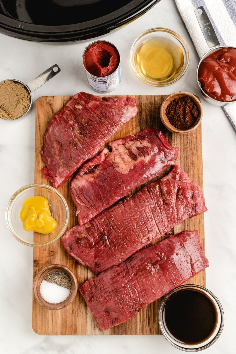 ingredients displayed for making barbecue beef sandwiches- steak cut into slices and condiments for sauce