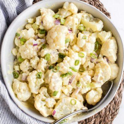 cauliflower potato salad in a white bowl on a striped napkin