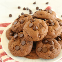Piled Chocolate Chocolate Chip Pudding Cookies on a white plate with a striped napkin