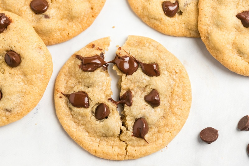 overhead shot of a chocolate chip cookie pulled apart to show gooey melted chocolate chips
