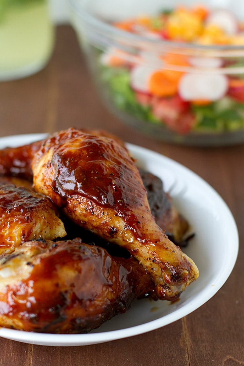 Oven Baked BBQ Chicken on a white plate with salad displayed in the background
