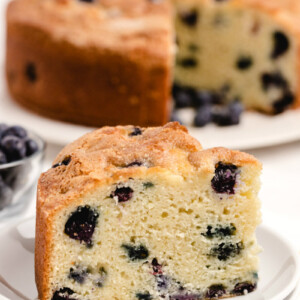 slice of buttermilk blueberry cake on a white plate with the rest of the cake on a white plate in the background