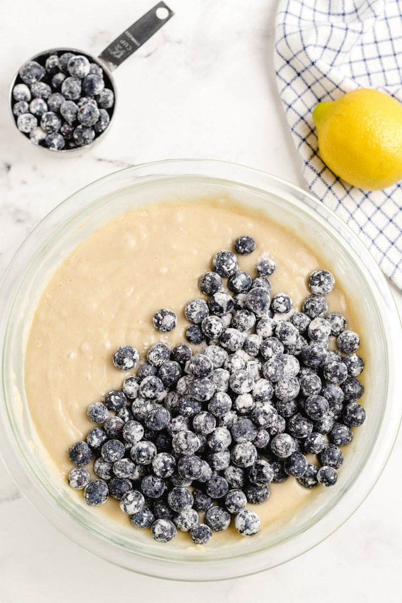 overhead shot of bowl of cake batter with blueberries added on top. more blueberries in a measuring cup on the side. lemon and gray/white dishtowel on the side too.