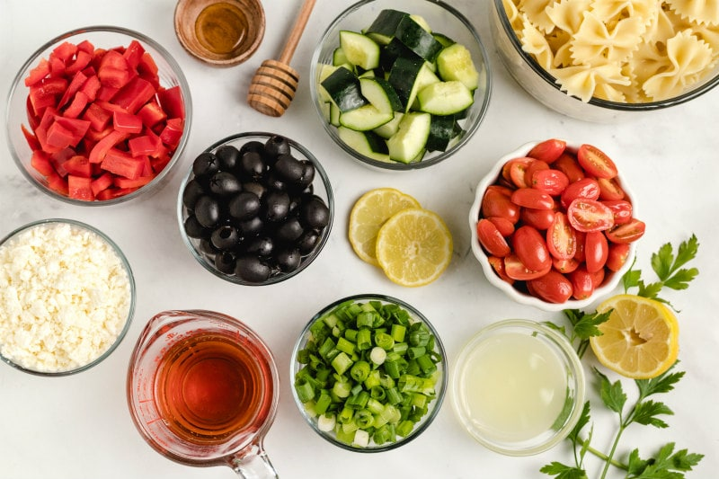 overhead shot of ingredients for bow tie pasta salad in display bowls