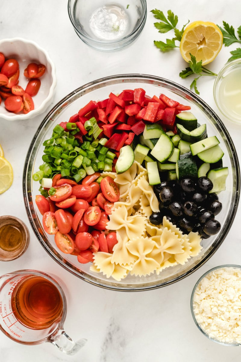 overhead shot of bow tie pasta salad ingredients in a glass bowl with dressing, cheese and tomatoes displayed in the background