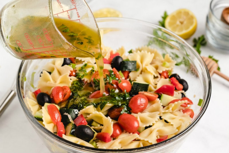 pouring vinaigrette from a measuring cup onto bow tie pasta salad in a glass bowl