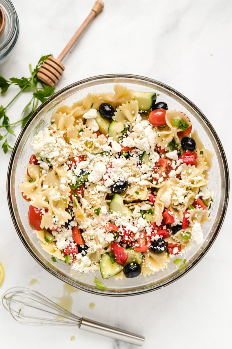 overhead shot of bow tie pasta salad in a glass bowl and feta cheese sprinkled on top. whisk and honey wand displayed in background