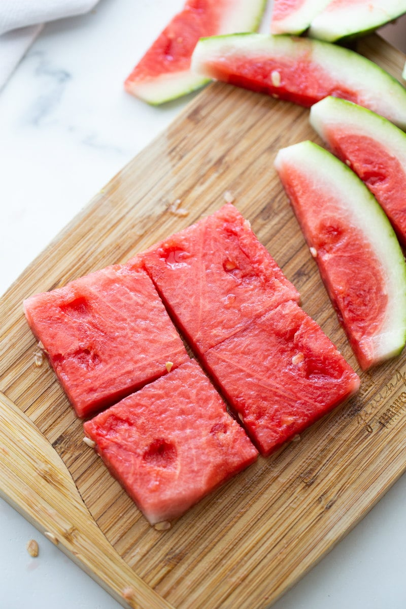 slices of fresh watermelon cut into squares on a cutting board
