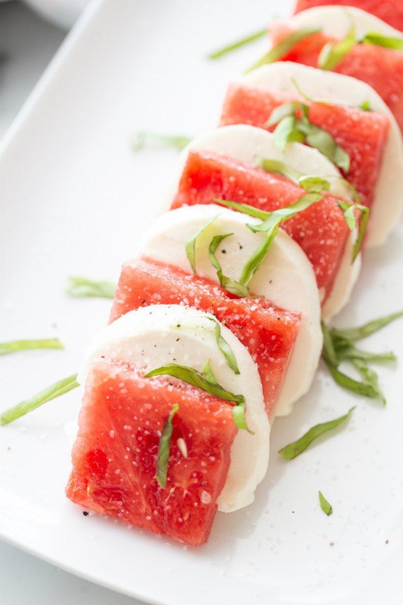 watermelon caprese salad on a white plate waiting to be topped with balsamic glaze