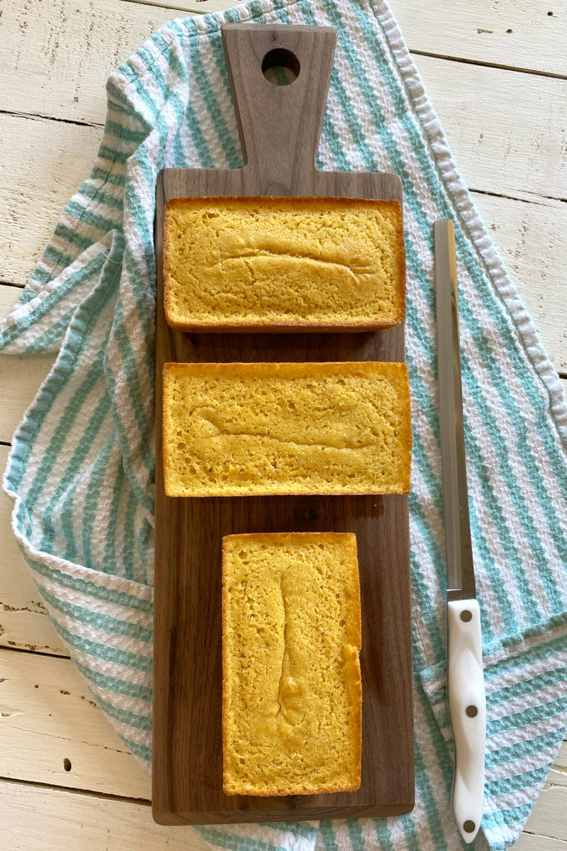 overhead shot of three mini loaves of buttermilk cornbread on a cutting board with a bread knife sitting alongside. set on a white/teal striped cloth napkin