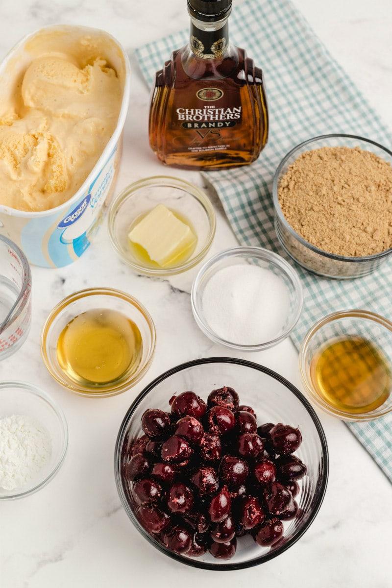 ingredients displayed for cherries jubilee ice cream pie in glass bowls: cherries, water, sugar, cornstarch, brandy, butter, honey, graham cracker crumbs and vanilla ice cream