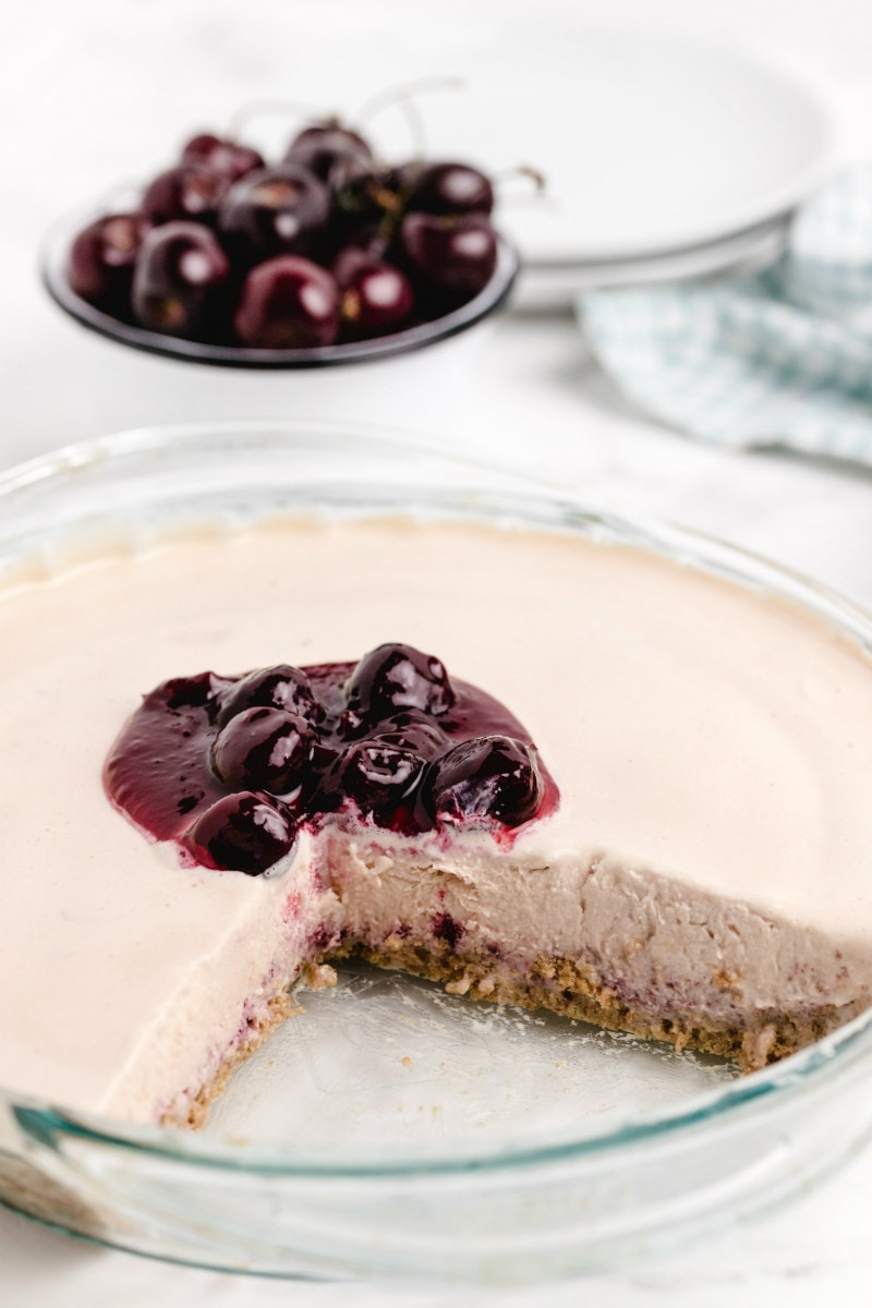 cherries jubilee ice cream pie in a pyrex pie plate with a slice cut out of it, cherry sauce on top and a bowl of fresh cherries in the background with stack of white plates and green/white checked cloth napkin