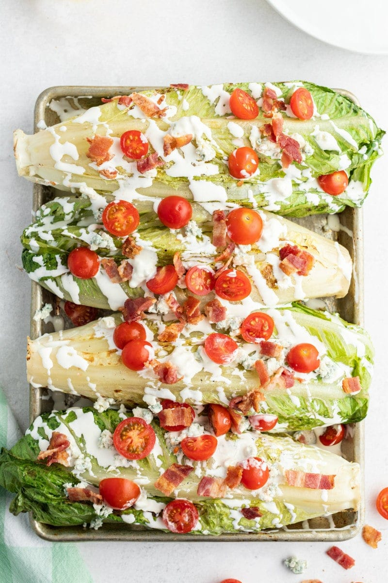 four grilled wedge salads displayed on a baking sheet