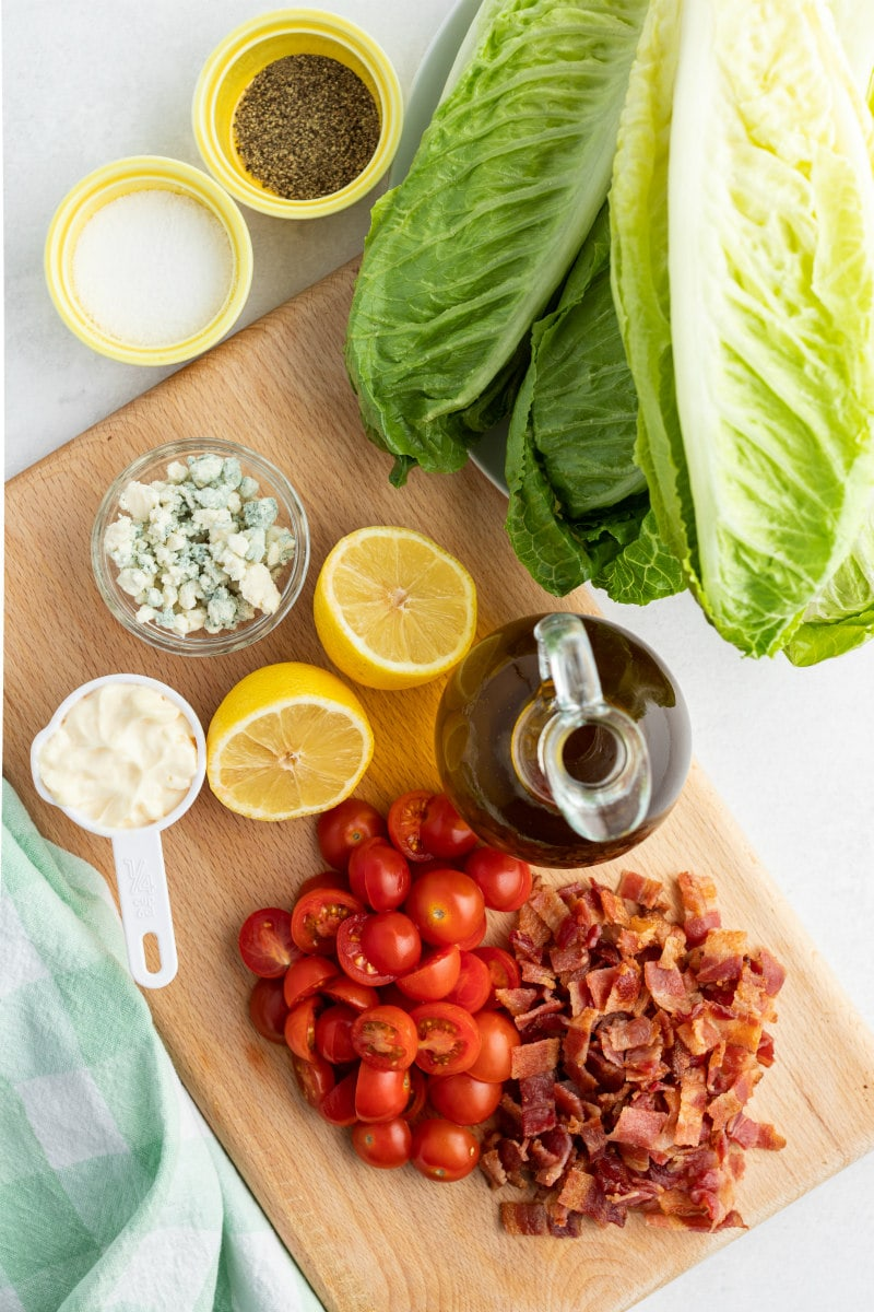 ingredients displayed for grilled romaine salad: romaine lettuce, mayonnaise, blue cheese, halved lemons, olive oil, tomatoes and bacon