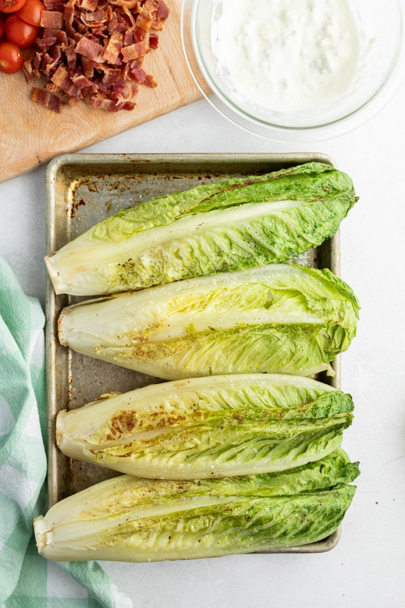 four grilled romaine lettuce heads on a sheet pan with a peek of chopped bacon and blue cheese dressing in the background