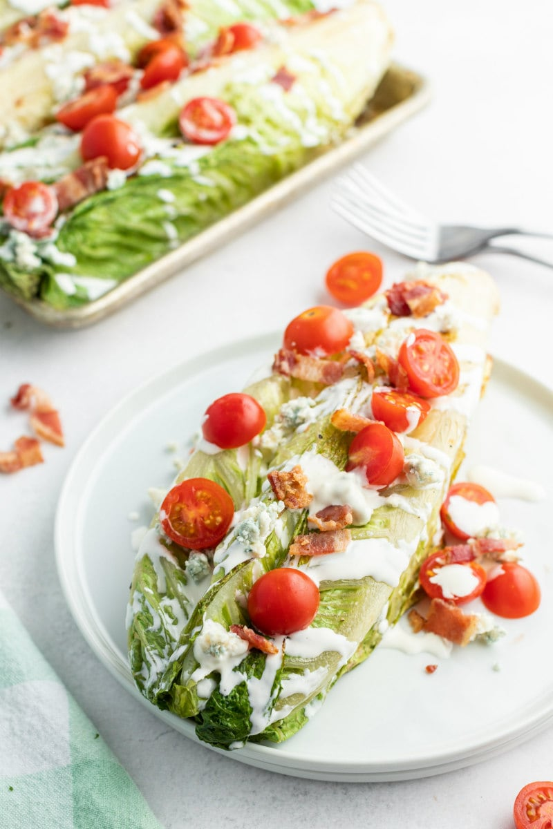 grilled wedge salad on a white plate with more wedge salad in the background