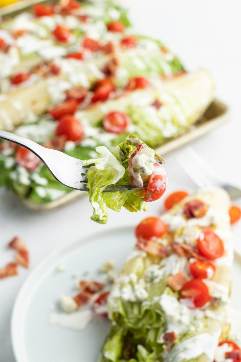 forkful of grilled wedge salad above a white plate of a serving of the salad and more wedge salads in the background