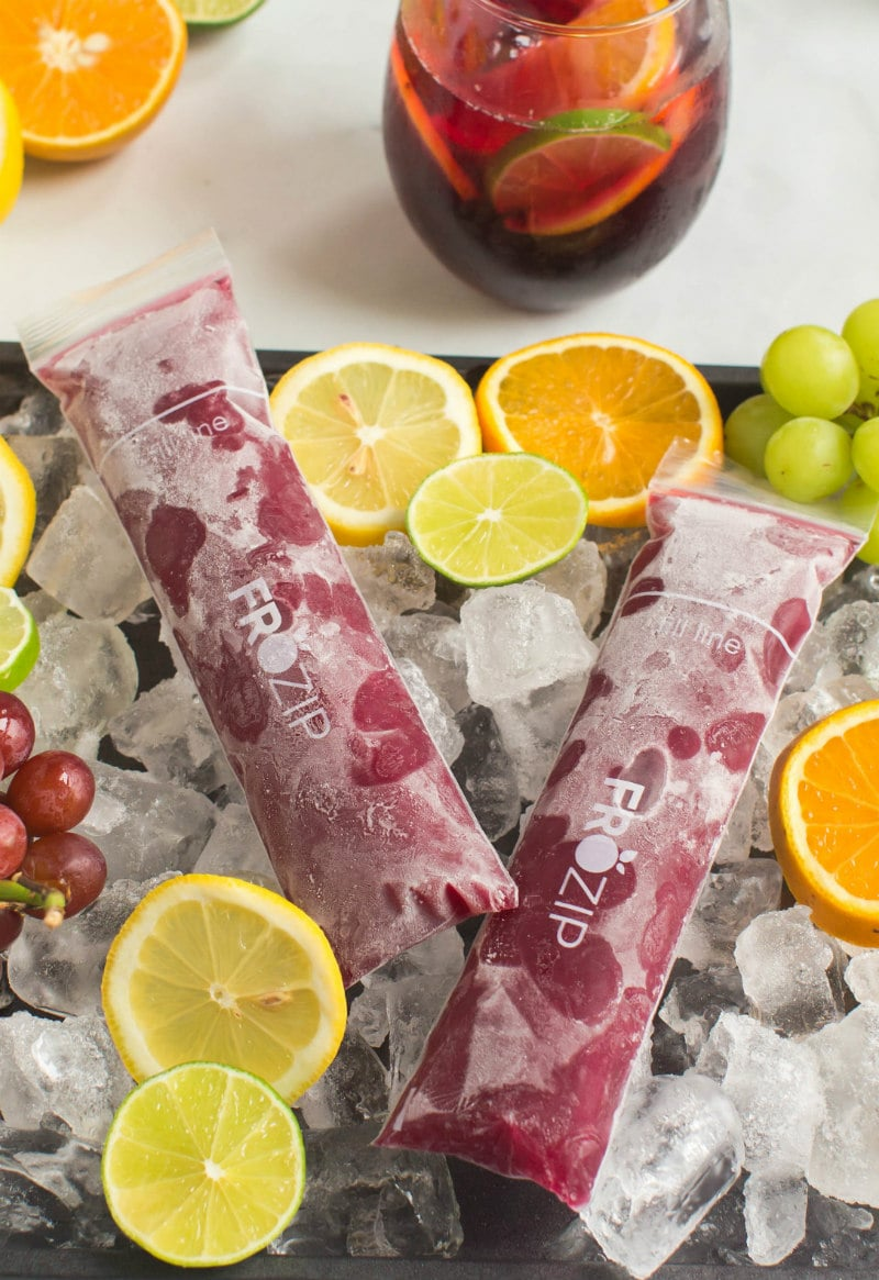 two sangria popsicles set on a tray of ice with sliced oranges, lemons and grapes and a glass of sangria in the background