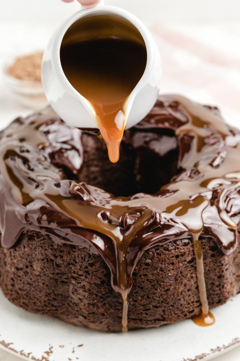 pouring caramel onto chocolate wasted cake from a white pitcher