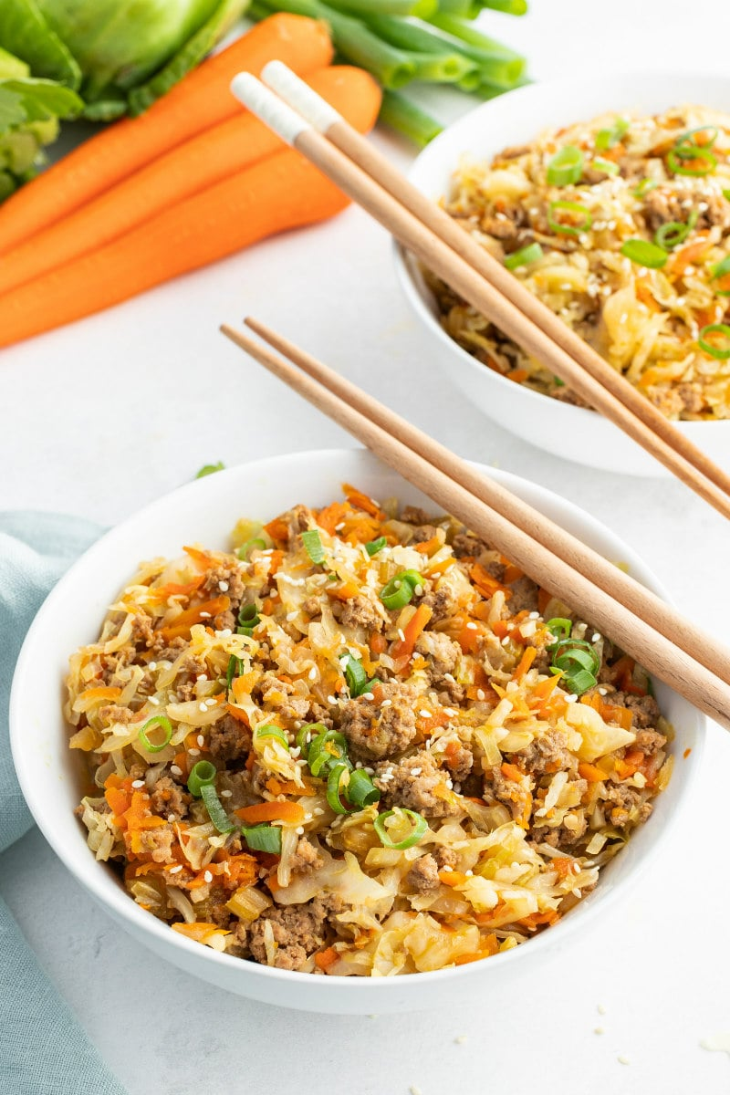 white bowl with egg roll and chopsticks