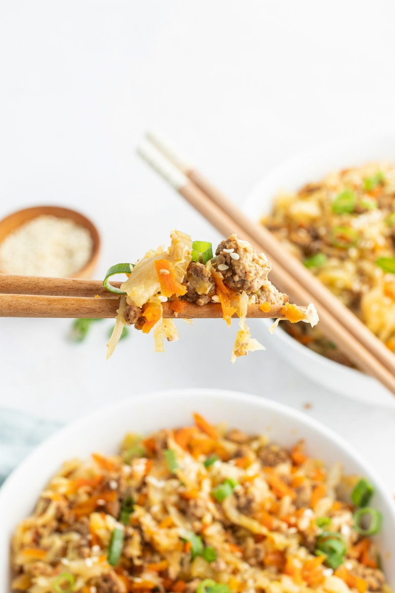 chopsticks with a bite of egg roll in a bowl