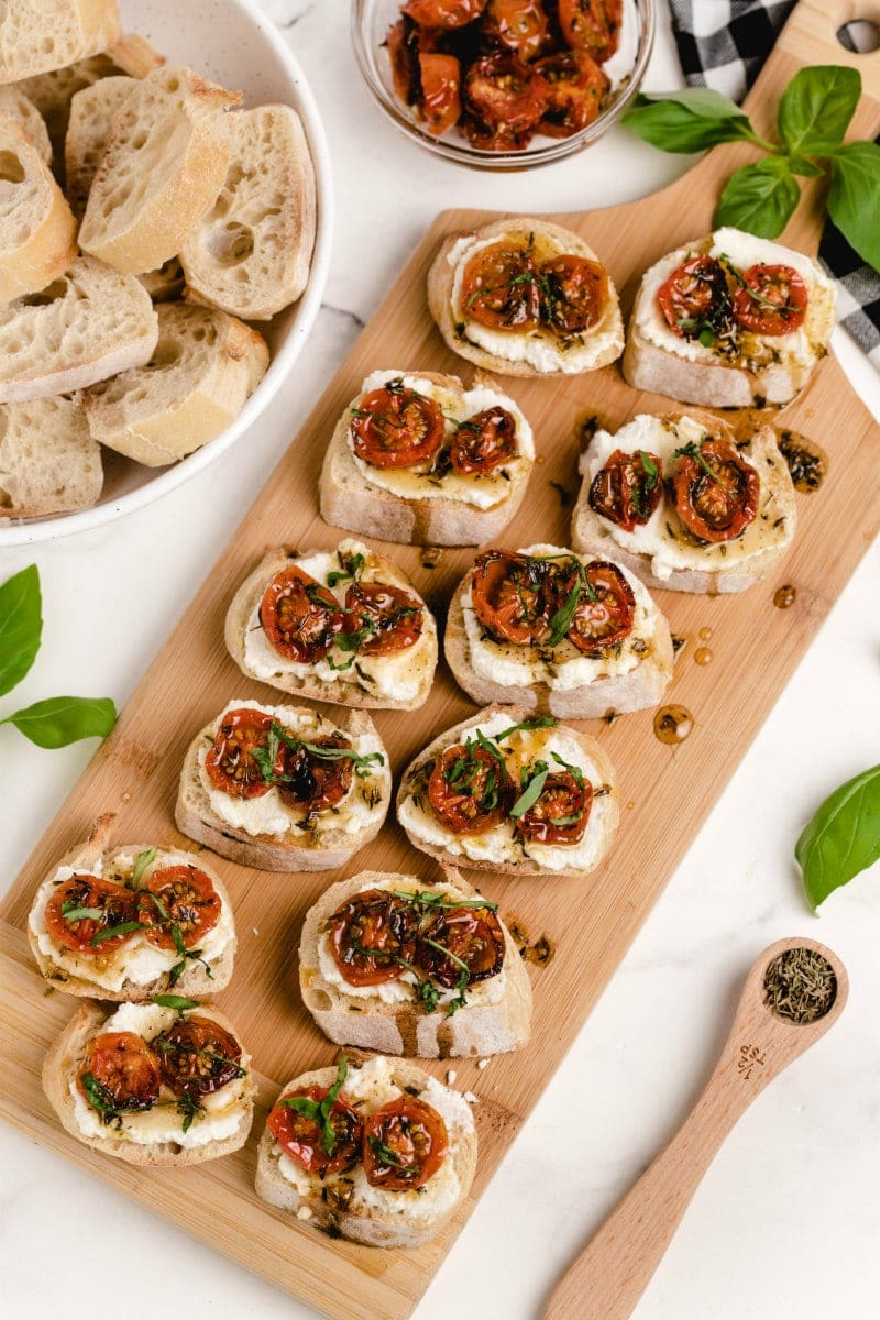honey tomato bruschetta with ricotta on a wooden board with a bowl of baguette slices and fresh basil on the side with a white and black checked napkin