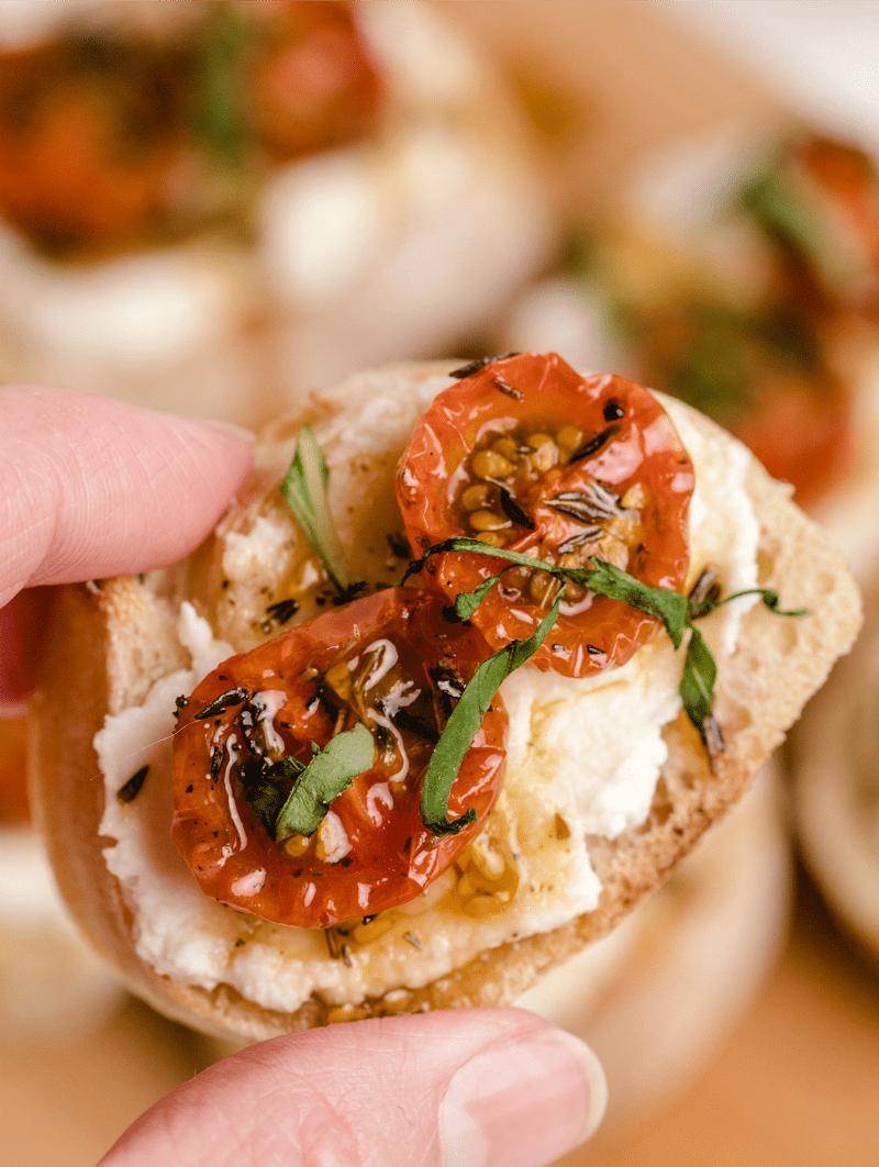 fingers holding a piece of honey tomato bruschetta with ricotta
