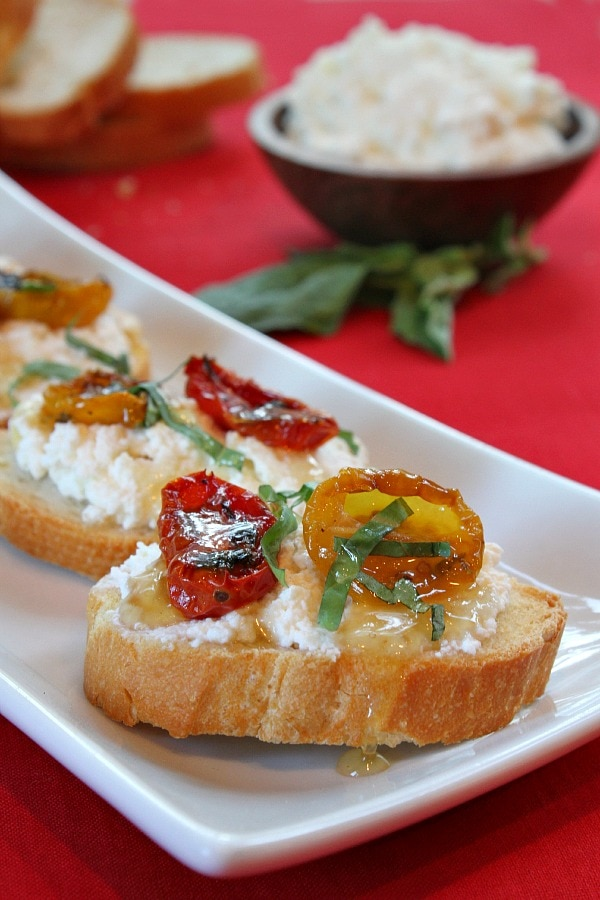 honey tomato bruschetta displayed on a white plate with fresh basil leaves on a red background