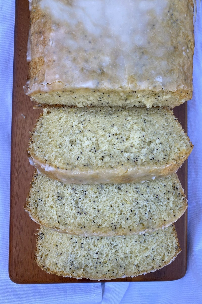 overhead shot of glazed lemon poppy seed bread cut into slices on a wood board