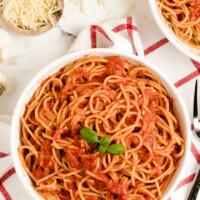 pasta pomodoro in a white bowl garnished with fresh basil
